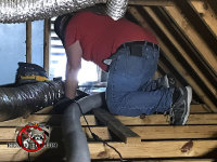 Animal control supervisor Dean Scott on his hands and knees vacuuming animal droppings from between the joists in an attic before installing new insulation