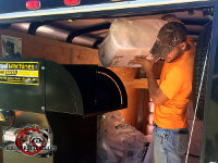 Technician inside a trailer feeding bales of insulation into a machine that aerates and shreds the insulation before pumping it through a hose into the attic of a house