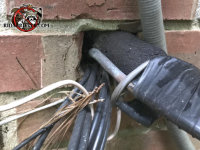 There is a gap around the air conditioning pipes and wires where they pass through a hole in the exterior brick wall of the house