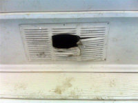 Crawl space vent with a big hole in it after DIY'er sealed raccoon inside house